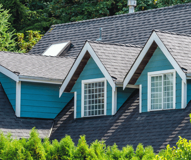 Newly constructed home painted blue with peaked roof and new shingles.